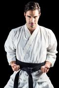 Portrait of fighter performing karate stance on black background - stock photo