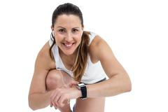 Portrait of athlete woman checking time in wrist watch on white background Stock Photos