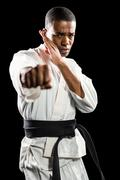 Portrait of fighter performing karate stance on black background Stock Photos