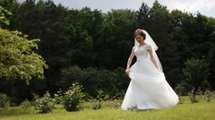 Beautiful brunette woman dancing and circling with bridal dress at the park - stock footage