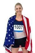 Athlete posing with american flag wrapped around his body on black background - stock photo