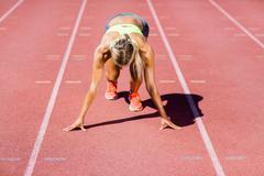 Female athlete ready to run on running track on a sunny day Kuvituskuvat
