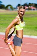Female athlete warming up on the running track on a sunny day Stock Photos