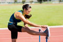 Female athlete warming up above hurdle on running track - stock photo