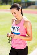 Happy female athlete using stopwatch on running track - stock photo