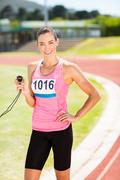 Portrait of female athlete standing on running track showing stopwatch - stock photo
