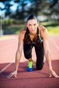 Portrait of female athlete in ready to run position on running track Kuvituskuvat