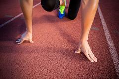 Female athlete in ready to run position on running track Kuvituskuvat