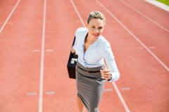 Businesswoman with briefcase in ready to run position on running track Kuvituskuvat