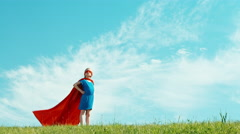 Super hero girl child 7-8 years old protects the world against the blue sky - stock footage