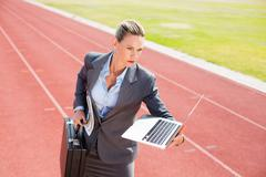 Businesswoman ready to run with a laptop and briefcase on running track Kuvituskuvat