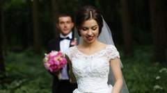 Beautiful smiling bride goes forward through the green park while groom with Stock Footage