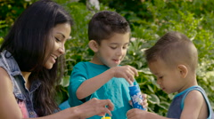 Mom blowing bubbles outside with her 2 young boys Stock Footage