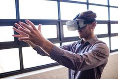 Businessman using virtual reality device - stock photo
