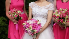 Beautiful bride standing between bridesmaids in pink dresses holding bouquets of Stock Footage