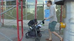Man walks infant son in stroller through construction on street - stock footage