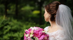 Smiling brunette bride wearing veil holding pink bouquet looking at camera in - stock footage