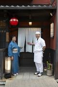 Senior Japanese hostess and cook smiling in front of Japanese restaurant - stock photo