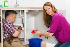 Male Plumber Repairing Pipe Under Sink While Woman Squeezing Cloth In Kitchen - stock photo