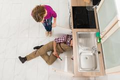 Male Plumber Repairing Sink While Woman Standing In The Kitchen - stock photo