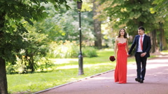 An elegant red dress wedding couple walking in the park - stock footage