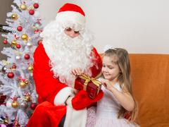 Girl unleashes a red ribbon gift that keeps Santa Claus in the hands of Kuvituskuvat