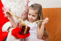 Girl unleashes a red ribbon gift in the hands of Santa Claus Kuvituskuvat