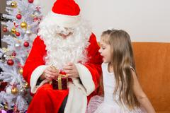 The girl with interest looks like Father Christmas helps to open her gift Stock Photos