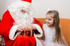 Santa Claus helps to untie the ribbon gift, little girl happily looking at hi Kuvituskuvat