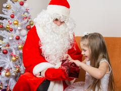 Little girl joyfully opens a gift that keeps grandfather frost Stock Photos
