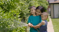 Mom with kids watering their garden Stock Footage