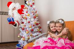 Two girls hug on the couch, santa claus peeping from behind trees Kuvituskuvat