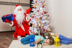 Santa Claus in New Years Eve was surprised seeing the tree two sleeping child Stock Photos