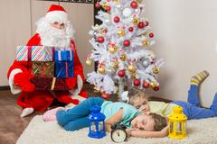 Santa Claus brought gifts for New Year's Eve and softened faces of the tw Kuvituskuvat