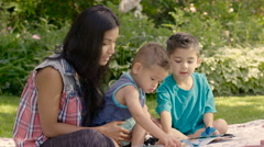Mom with 2 young sons reading together in yard, close up Stock Footage