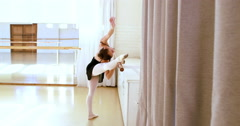Ballerina from the back is doing exercises with a bar Stock Footage