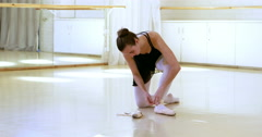 Portrait of ballerina is sitting and is putting on her dance shoes Stock Footage