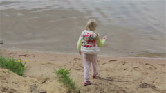 Little girl is washing her hands in the lake water on a sand beach. Stock Footage