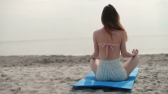 Woman meditating on beach in lotus position - stock footage