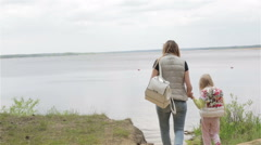 Pregnant woman and small girls are on the beach of a forest lake. Stock Footage