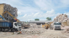 Demolition of factory building, machines clearing rubble on construction site. Stock Footage
