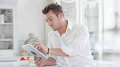 4K Portrait attractive smiling man relaxing at home with computer tablet. Stock Footage