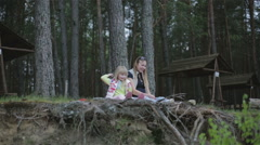 Little girl and her pregnant mother are sitting on a cliff in the forest. Stock Footage