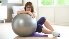 Senior woman sitting by fitness ball Stock Footage