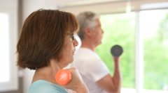 Senior people in gym lifting dumbbells - stock footage