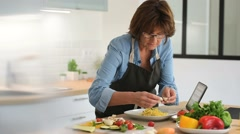 Senior woman in home kitchen preparing dish Stock Footage