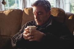 Portrait of man drinking cup of tea while relaxing in living room - stock photo