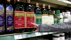 Woman selecting Spectrum organic olive oil in Save on Foods store - stock footage