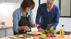 Senior couple in kitchen cooking together - stock footage