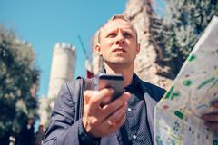 Tourist man try navigate himself with map and smartphone in unknown city - stock photo
